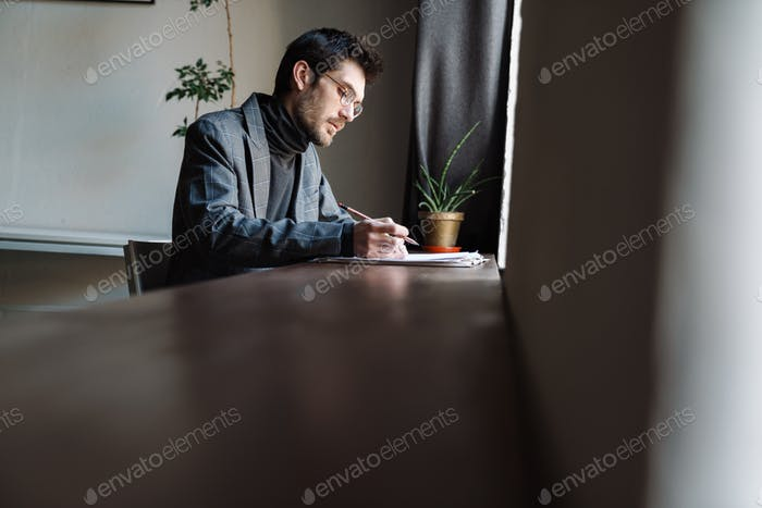 Image of handsome unshaven young businessman examining documents