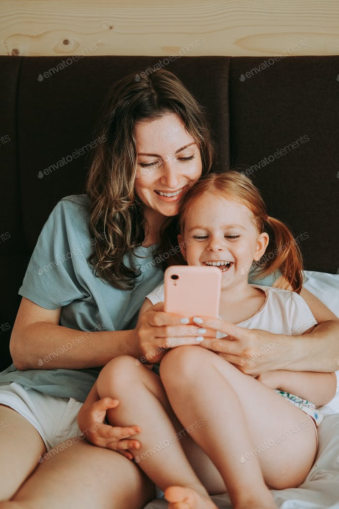 Mother and her daughter use smartphone