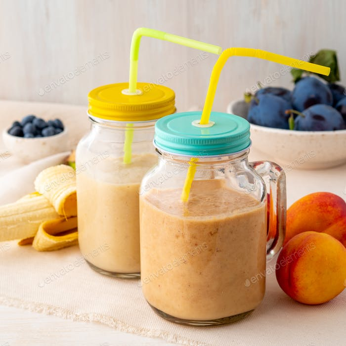 banana peach nectarine smoothie in two jars, fresh fruit milkshakes on white rustic wooden