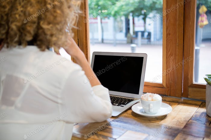 Rear view of woman using laptop in cafeteria