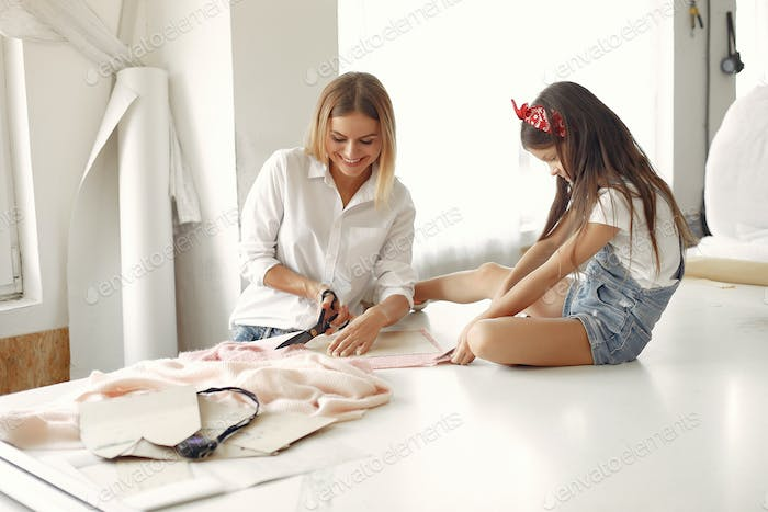 Mother with little daughter measure the fabric for sewing