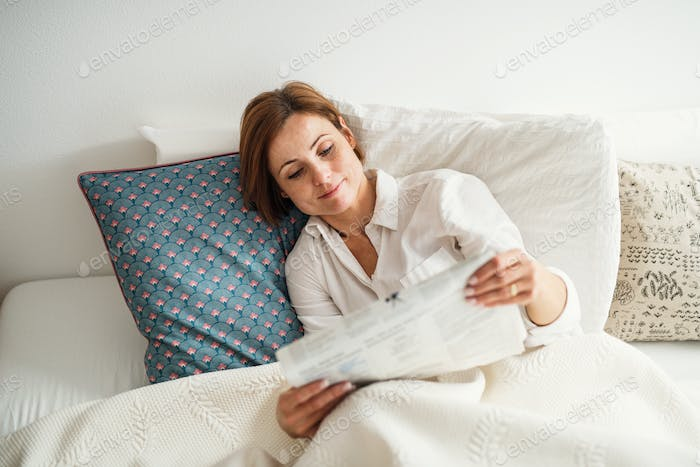 A young woman reading newspapers in bed in the morning in a bedroom.