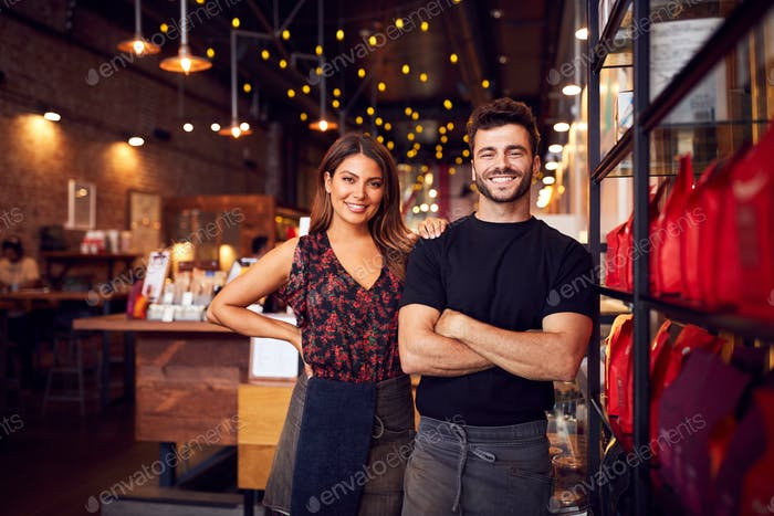 Portrait Of Male And Female Coffee Shop Owners Standing At Sales Desk