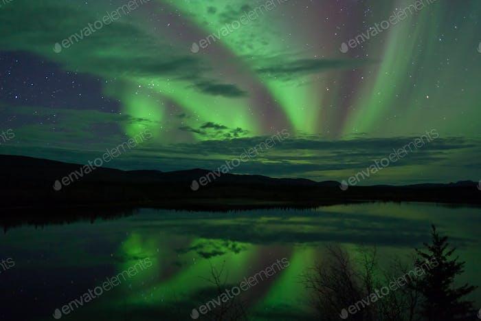 Dramatic Northern Lights calm lake mirrored