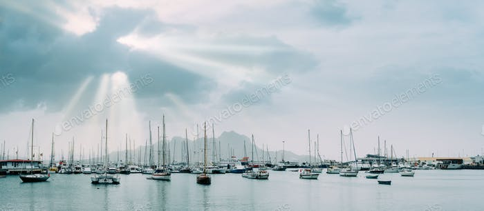 Sailboats and pleasure boats in the porto grande bay of the historic city Mindelo. Sunrays