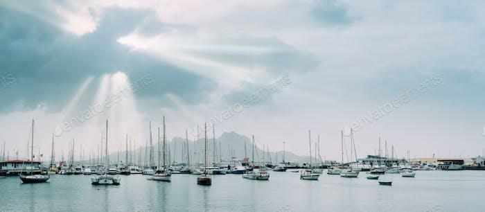 Segelboote und Freizeitboote in der Porto grande Bucht der historischen Stadt Mindelo. Sonnenstrahlen