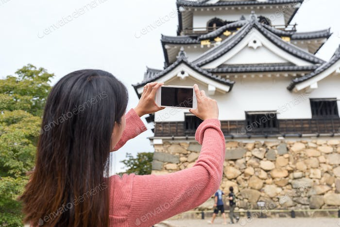 Back rear view of woman taking photo on Hikone Castle