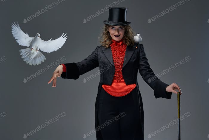 Woman in old fashioned costume with two pigeons and stick in studio