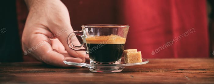 Espresso coffee. Waiter serving a glass cup on wooden table, banner