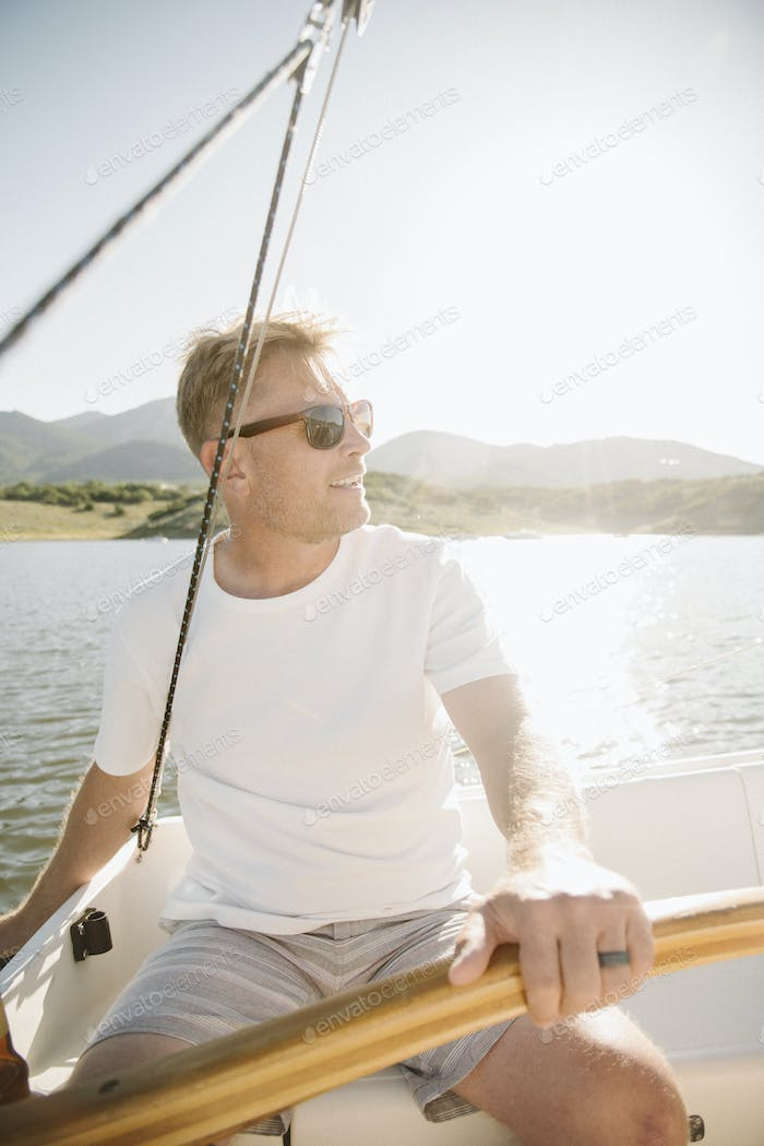 Portrait of a blond man with sunglasses steering a sail boat.