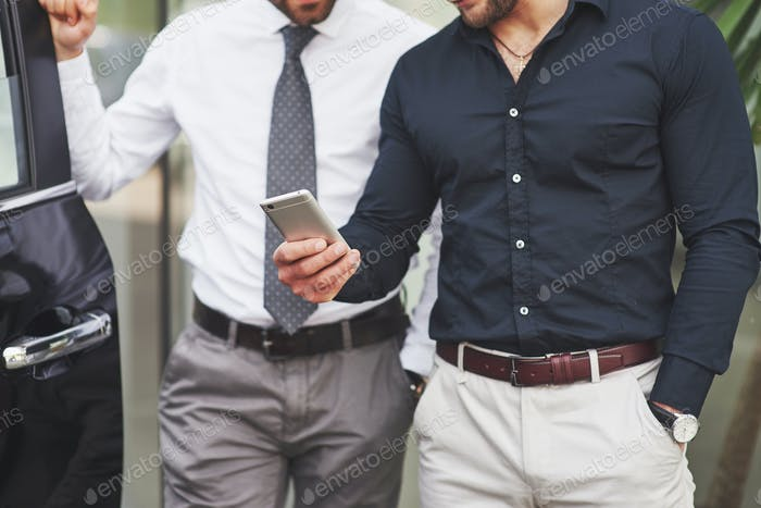 Два счастливых, уверенных молодых бизнесмена стоят у офиса