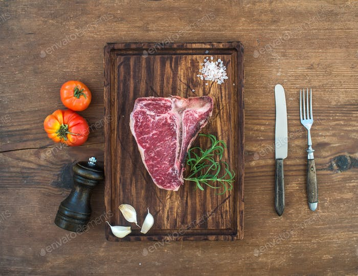 Raw fresh meat t-bone steak with garlic cloves, tomatoes, rosemary, pepper and salt