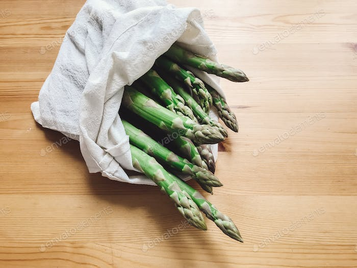 Reusable eco friendly bag with fresh asparagus on wooden table