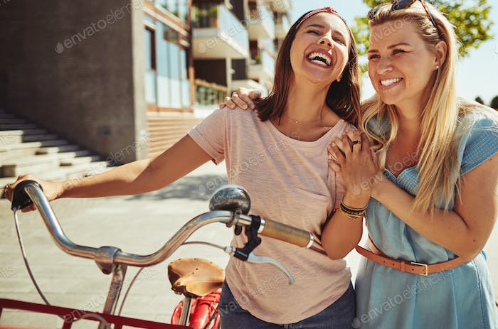 Friends laughing while walking with their bike in the city