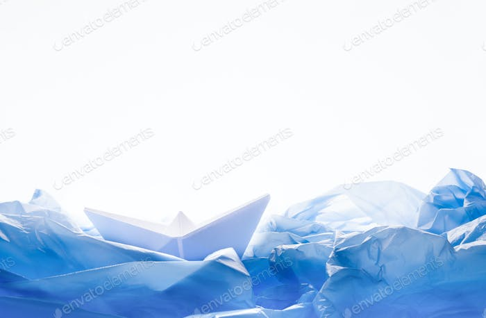 Paper boat in water of plastic bags over white background