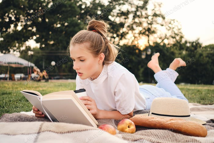 Young attractive serious woman lying on plaid thoughtfully reading book on picnic in city park