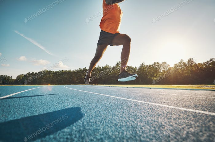 Athlete in mid air while sprinting down a running track