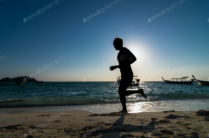 silhouette of running at sunrise time over the sea beach