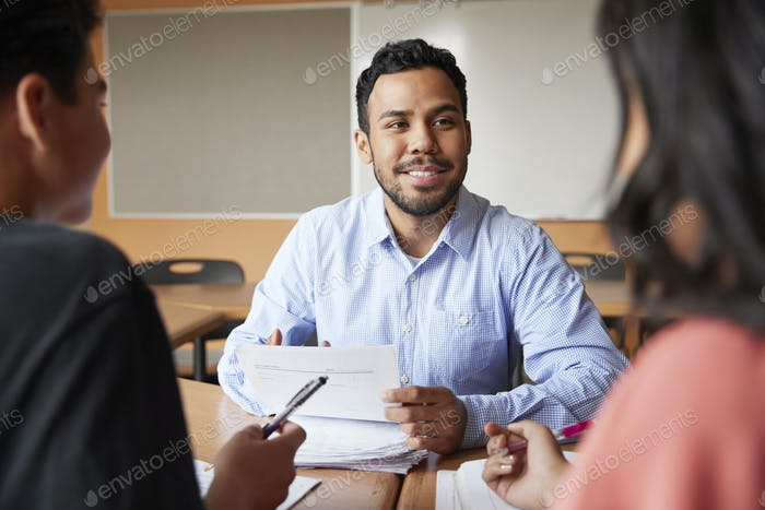 Male High School Tutor With Two Students At Desk In Seminar