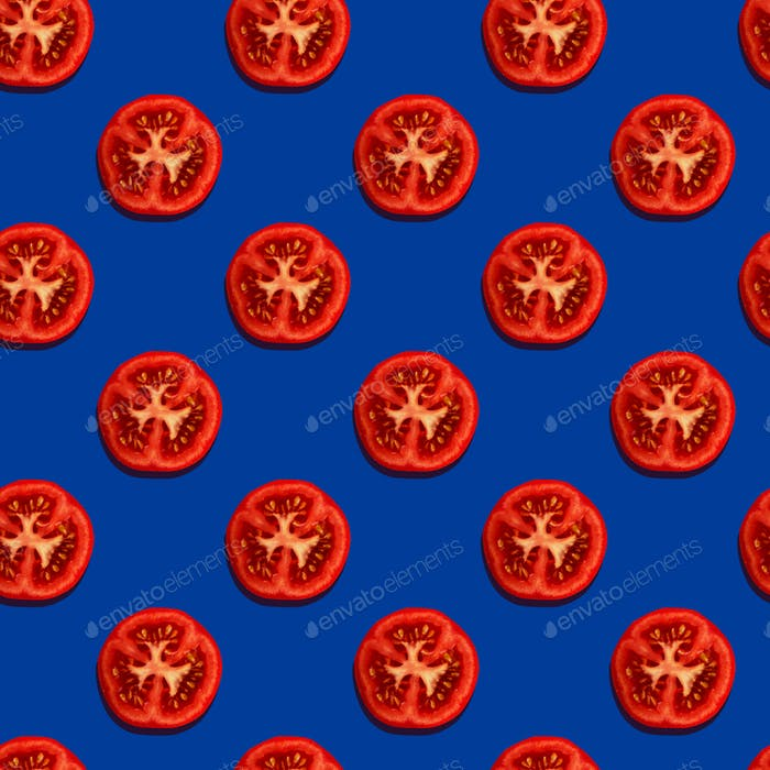 Seamless pattern with tomato slices on a blue background. Modern style concept