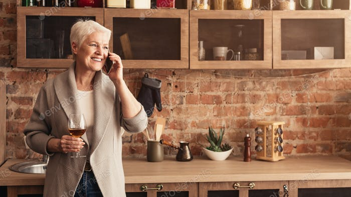Happy Elderly Woman Holding Glass Of Wine And Talking On Cellphone