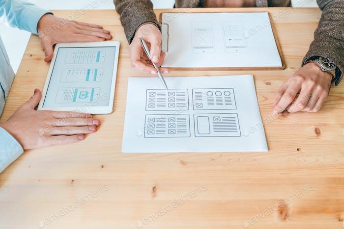 Hände von zwei jungen Designern diskutieren Layouts neuer Websites