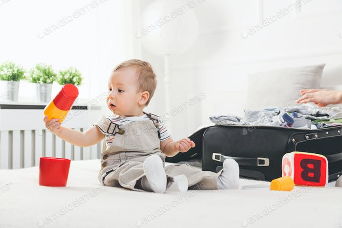 Travelling with kids. Cute toddler packing clothes and toys for holiday