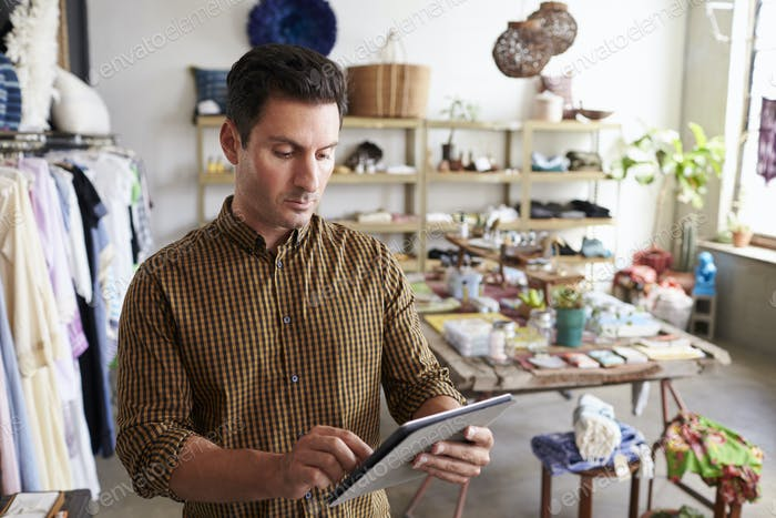 Male manager using tablet computer in clothes shop