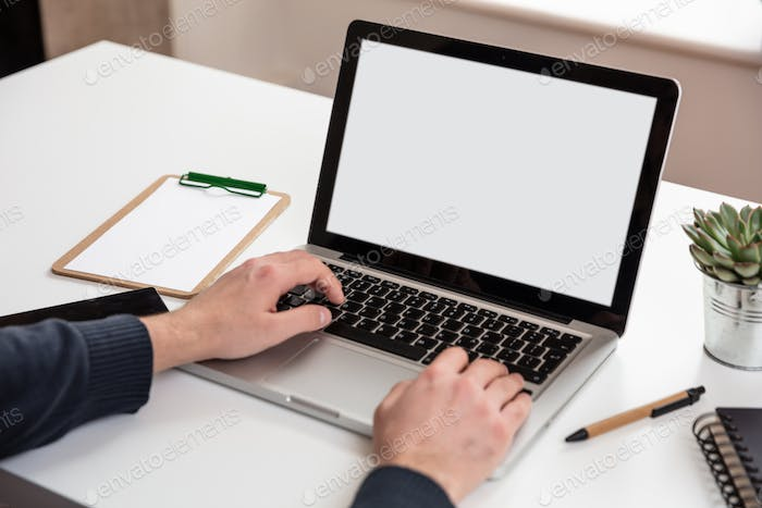 Laptop with white blank screen on a wooden desk