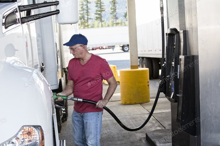 Caucasian man truck driver putting diesel fuel in his truck at a truck stop.