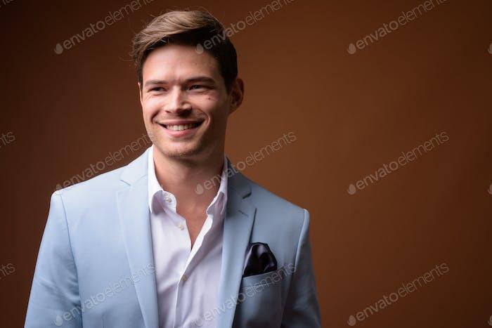 Studio shot of young handsome businessman in suit