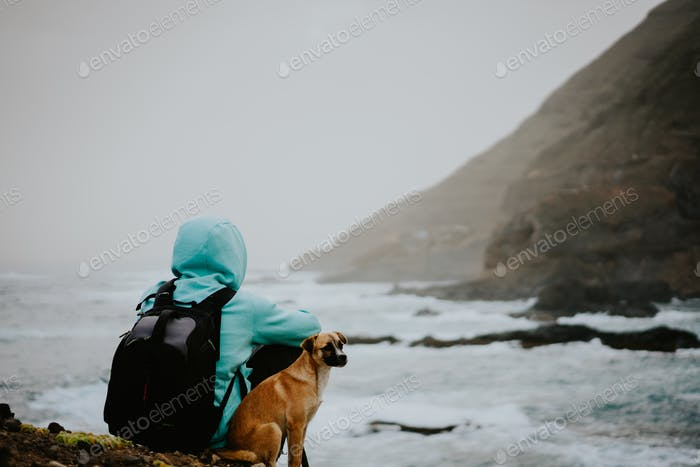 Man with a dog in front of rural coastline landscape with mountains in a fog and ocean waves hitting