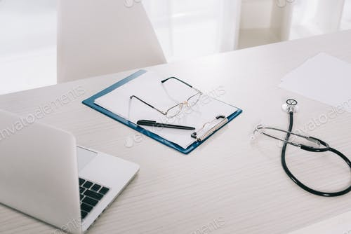 glasses and pen on clipboard on working table in hospital