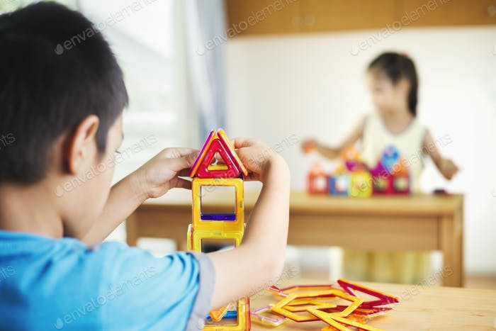 Two children building using geometric shapes.