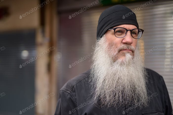 Face of mature handsome bearded man thinking in the streets outdoors