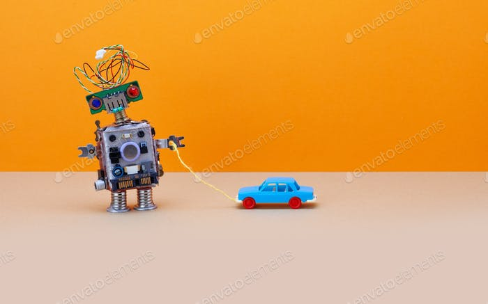 Robot plays with a vintage toy car. Orange background, copy space