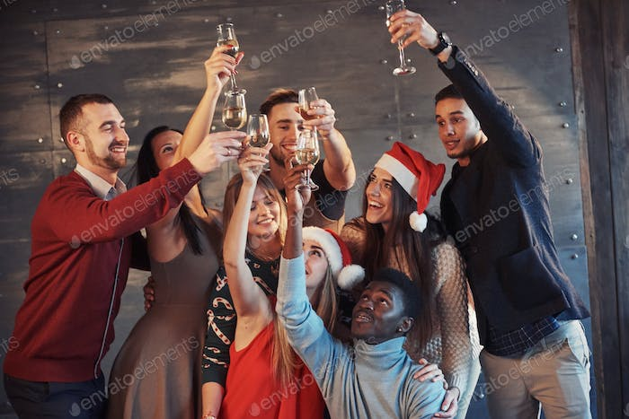 Group of cheerful young multiethnic people in Santa hats on the party