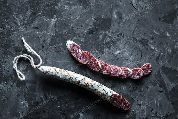 Slices of french saucisson/salami on a grey background