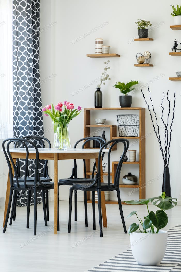 Industrial dining room interior with a table, black chairs, pink