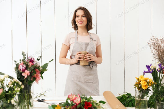 Pretty smiling florist woman with different flowers