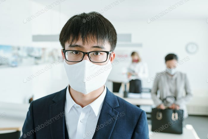 Young elegant Chinese businessman in eyeglasses, protective mask and suit