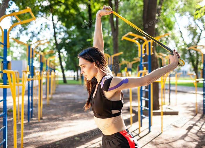 Профессиональная спортсменка позирует с резинками на открытом воздухе