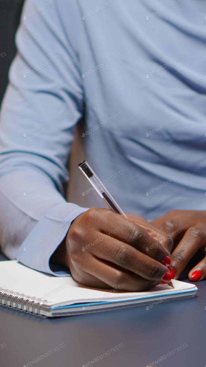 Close up of african businesswoman writing list of tasks