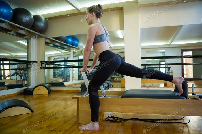 Determined woman performing stretching exercise on reformer