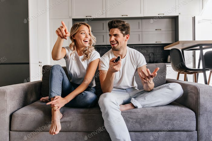 Interested blonde lady watch TV. Indoor photo of smiling couple sitting on cozy couch