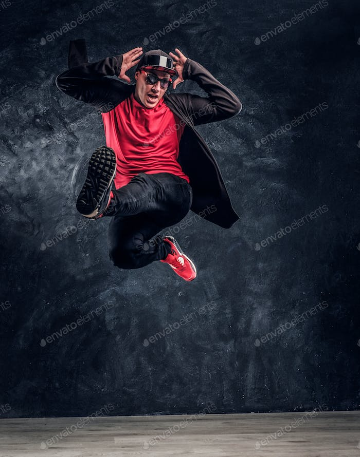 Emotional stylish dressed guy performing break dance jumping.