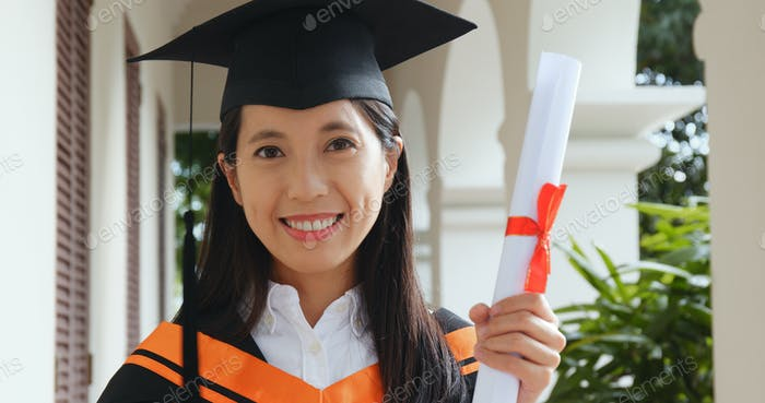 Excited woman wearing graduation gown in university campus