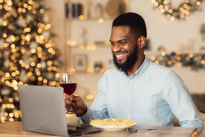 Black man having dinner drinking wine making videocall
