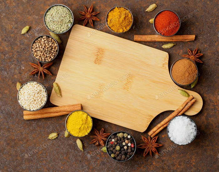 Various Indian spices in metal cups. Empty wooden Board, top view, space for text.