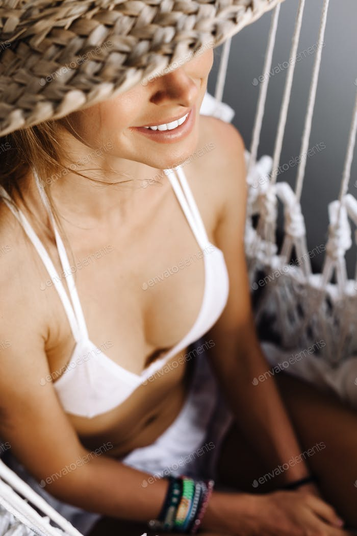 woman wearing white bikini sitting in hammock